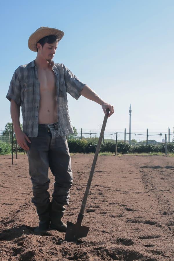 Landbouwerskerel met schop op vrije grond stock fotografie