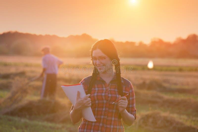 Landbouwersmeisje op gebied bij zonsondergang stock foto's