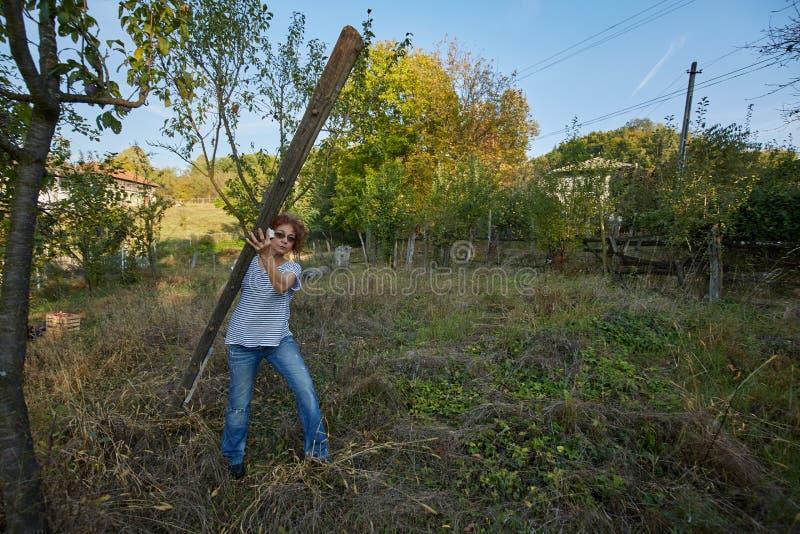 Landbouwersvrouw met een ladder in de boomgaard royalty-vrije stock foto's