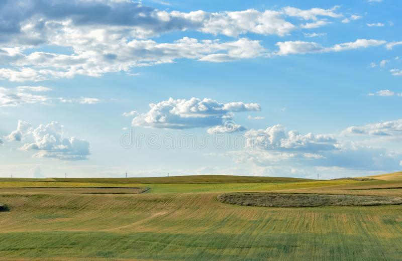 Landbouwgrond met blauwe en bewolkte hemel stock fotografie
