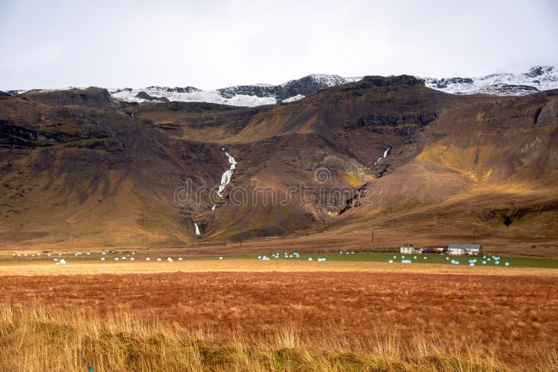 Landbouwgrond met Verpakt Hay Bales bij de Bodem van Majestueuze Bergen wordt gestippeld die stock afbeelding