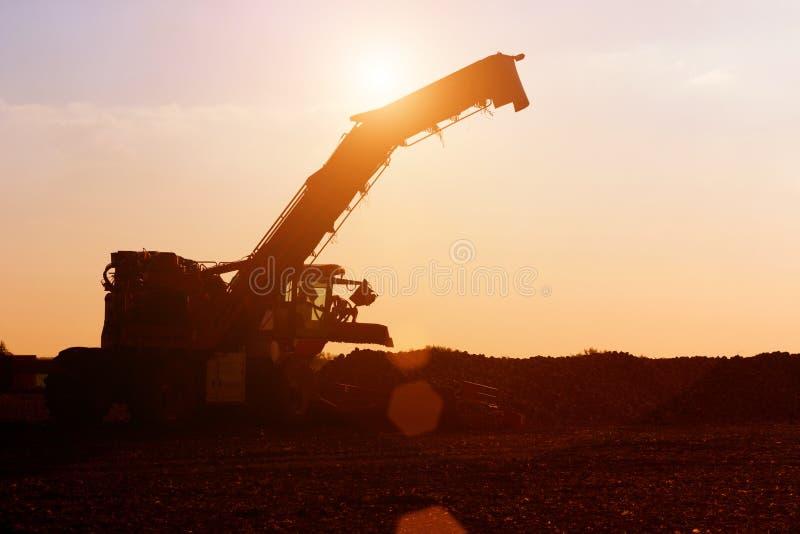 Landbouwmachines in de zonsondergang stock foto's