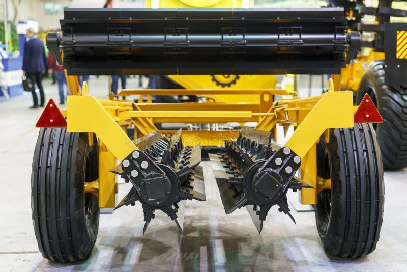 Landbouwmachines in landbouwmarkt Nieuwe landbouwmachines bij de tentoonstelling Rode tractor dicht omhooggaand o van ploeg de mo stock foto's