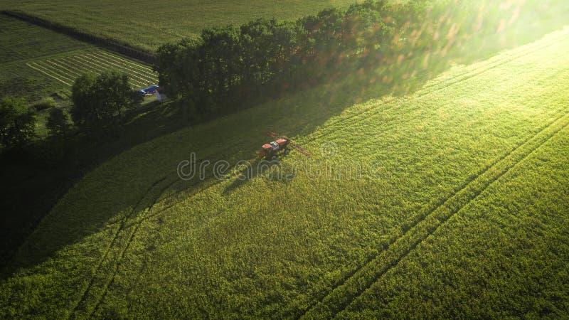 Landbouwmachines op het gebied Tractor met een spuitbus Lucht Mening stock afbeelding