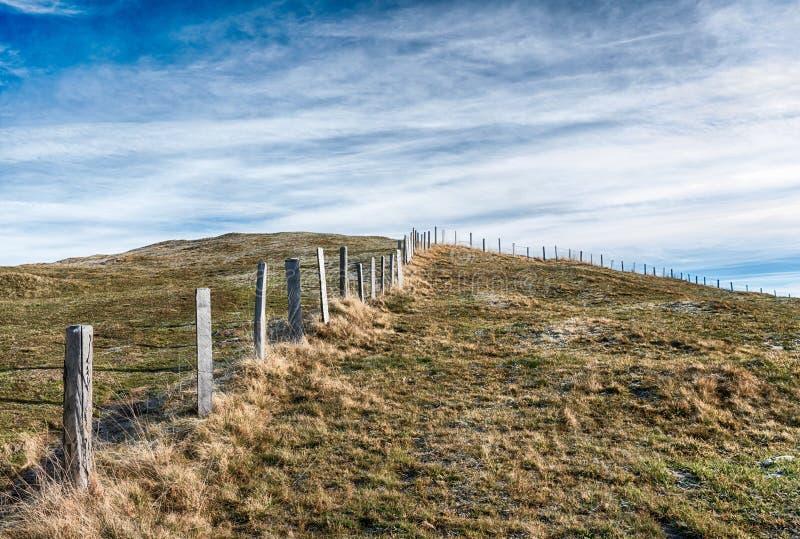 Landcape för öppet land med den gräs- ängen och väg och rimfrost och is och gammalt träkors i mitt under en expansivt himmel och  royaltyfria bilder