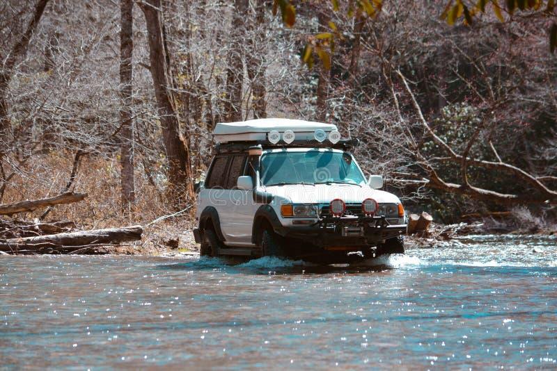 Landcruiser van-roading op een rivier stock foto