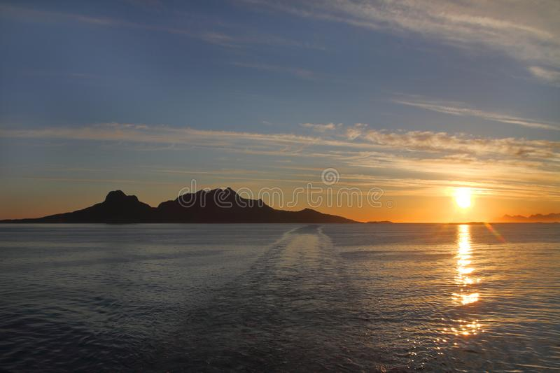 Landegode island and the midnight sun. Midnight sun seen from Vestfiorden,Island of Landegode close-up the mountains of Lofoten islands on the background royalty free stock image