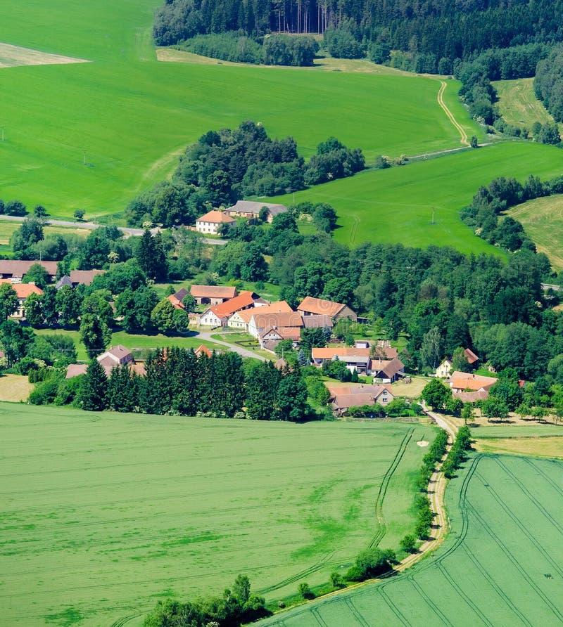 Landelijk de zomerlandschap met dorp op groen grasgebied royalty-vrije stock afbeeldingen