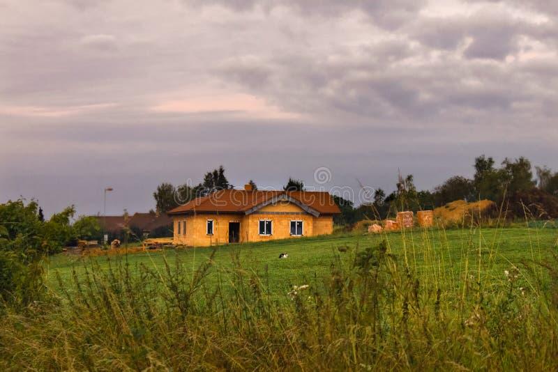 Landelijk landschap met bewolkte hemel en het rode huis van de dakbaksteen royalty-vrije stock afbeeldingen