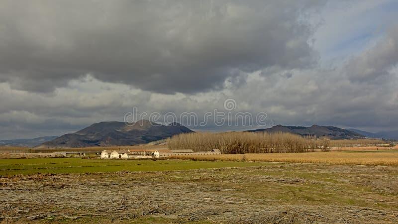 Landelijk landschap met landbouwbedrijf en Sierra Nevada -bergen op de achtergrond onder donkere grijze wolken royalty-vrije stock foto