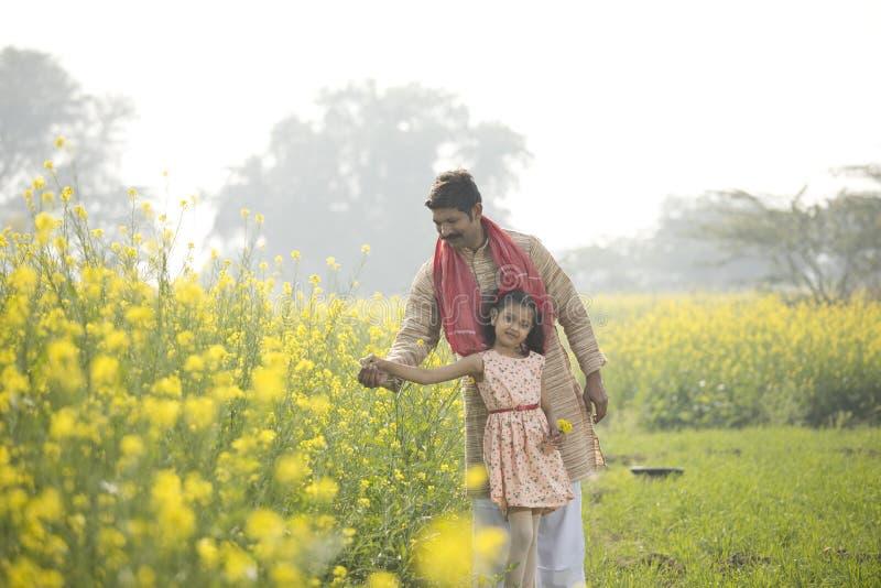 Landelijke landbouwer met haar dochter op raapzaadgebied stock afbeelding