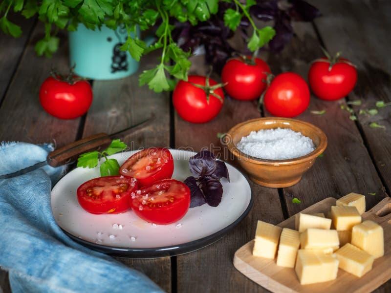 Landelijke schets, een kleine lunch van kaas en rode tomaten Peterseliegreens in een ceramische mok, denimservet op een oude hout stock afbeeldingen