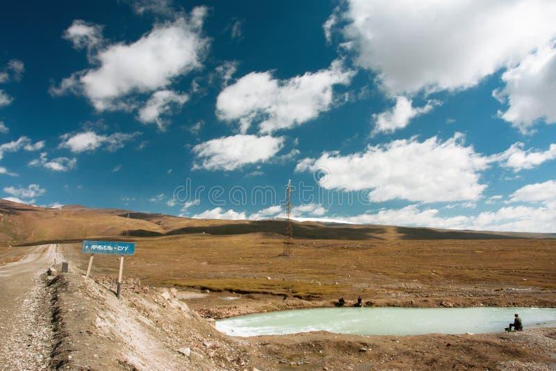 Landelijke weg met bergrivier en vissers onder witte wolken blauwe hemel royalty-vrije stock foto