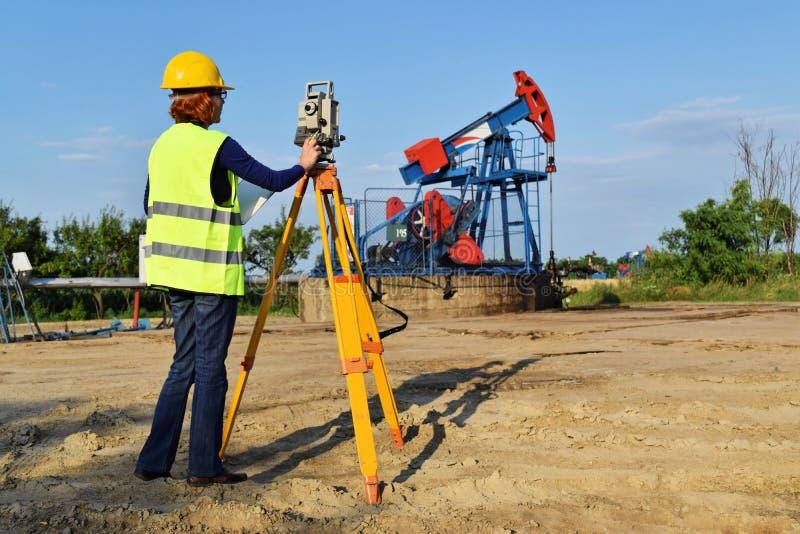 Landen Sie Feldmesserexperten bei der Arbeit über eine Ölquelle stockbilder