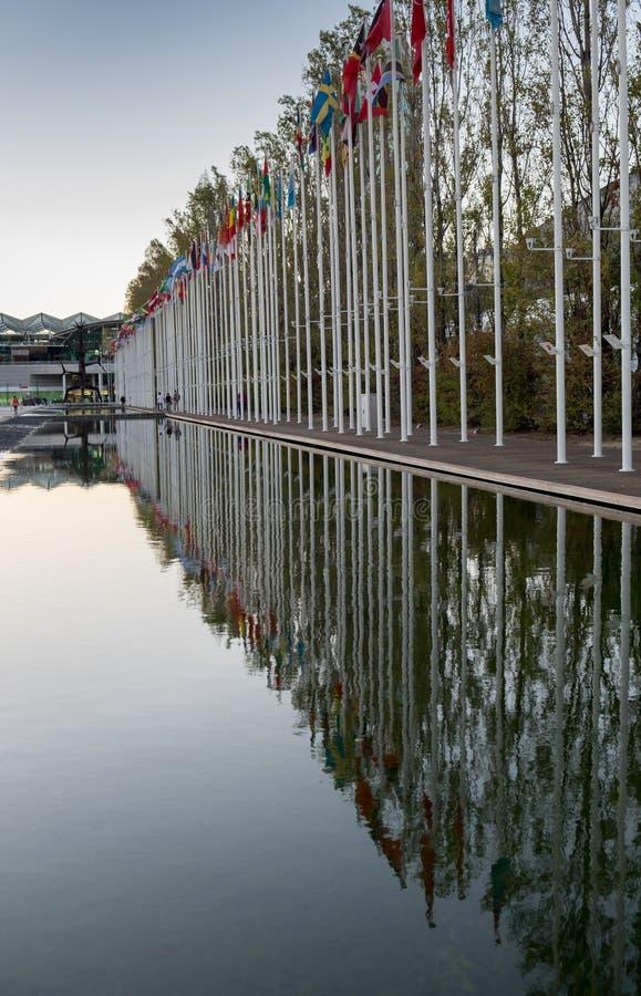 Landen van de wereldvlaggen in het water worden weerspiegeld dat Rossiodos Olivais - het Vierkante Park van Olive Grove van Natie royalty-vrije stock fotografie