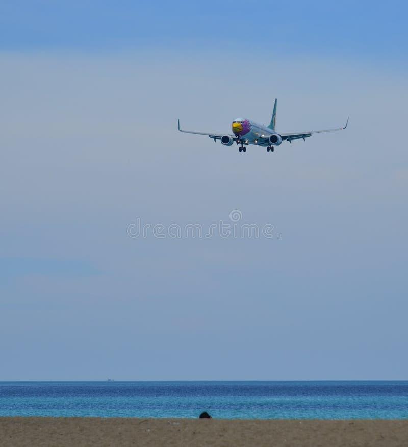 Landende vliegtuigen boven het strand stock foto's