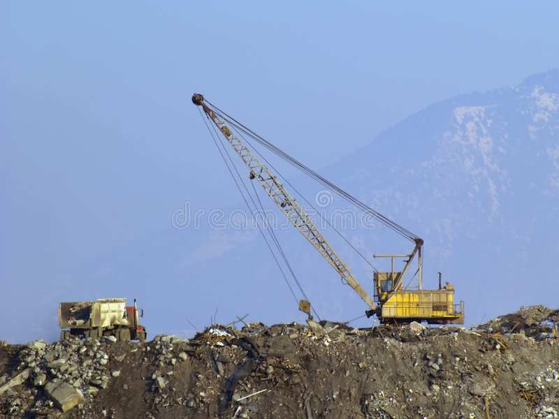 Landfill reclamation. Landfill heap environmental reclamation project with truck and shovel royalty free stock images