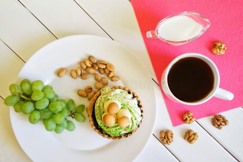 Landfr?hst?ck auf wei?en Brettern: Weintraube, Kuchen, Pistazien, Waln?sse, Kaffee und Milch stockfotografie