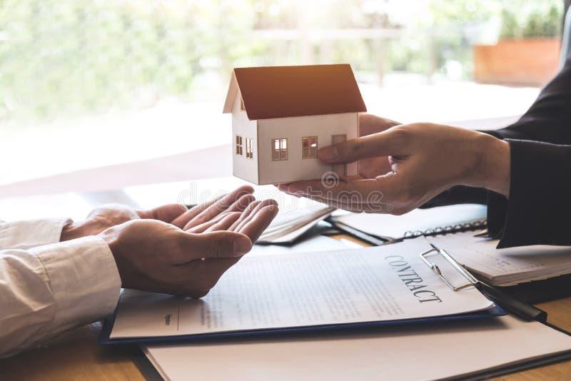 Landgoedagent die huismodel verzenden naar cliënt na het ondertekenen van onroerende goederen overeenkomstencontract met goedgeke stock foto's