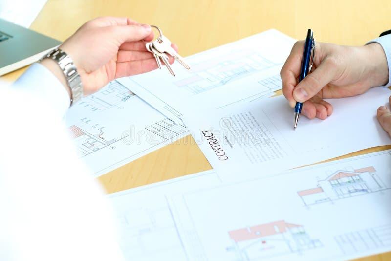 Landgoedagent die sleutels geven aan de bedrijfsman tijdens het ondertekenen van een contract stock foto
