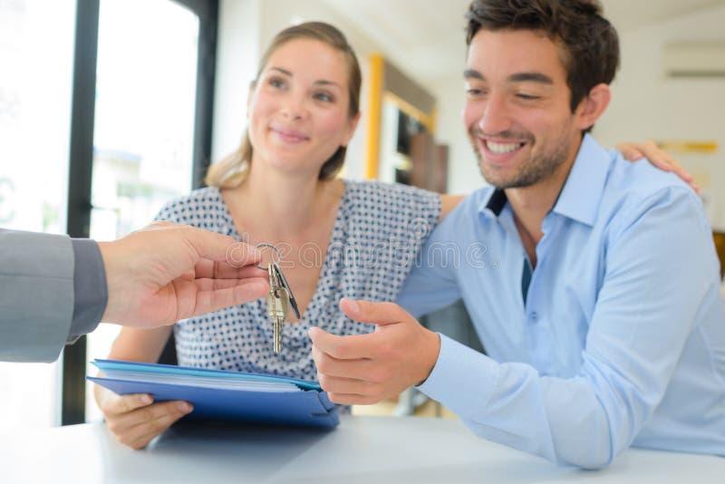 Landgoedagent die sleutels overhandigen aan gelukkig paar royalty-vrije stock afbeeldingen