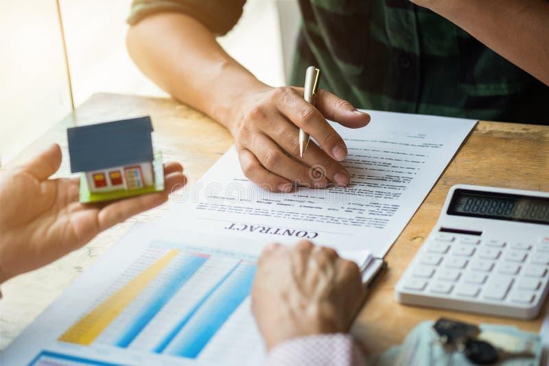Landgoedagent die vinger op document richten die totale kosten tonen die een document document voor het kopen van huis onderteken stock foto