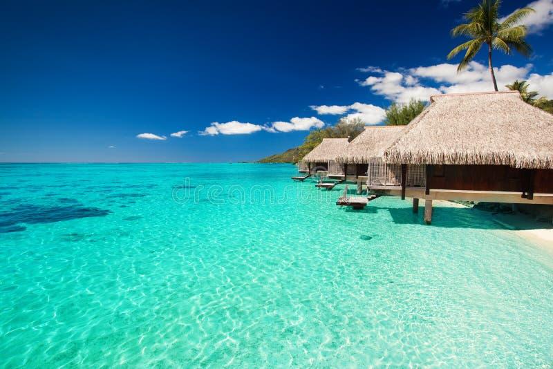 Landhäuser auf dem tropischen Strand mit Jobstepps in Wasser lizenzfreie stockfotos
