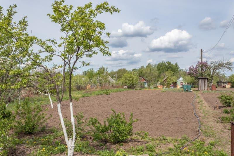 Landhaus mit der Anbaufl?che im Fr?hjahr umgeben durch Gr?n in Russland Russische Datscha stockfotografie