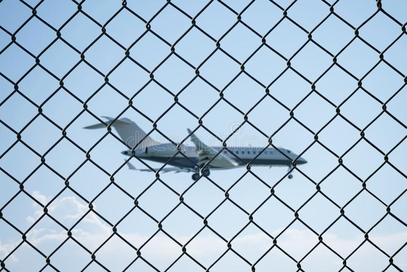 Landing airplane behind mesh wire fence at the airport royalty free stock image