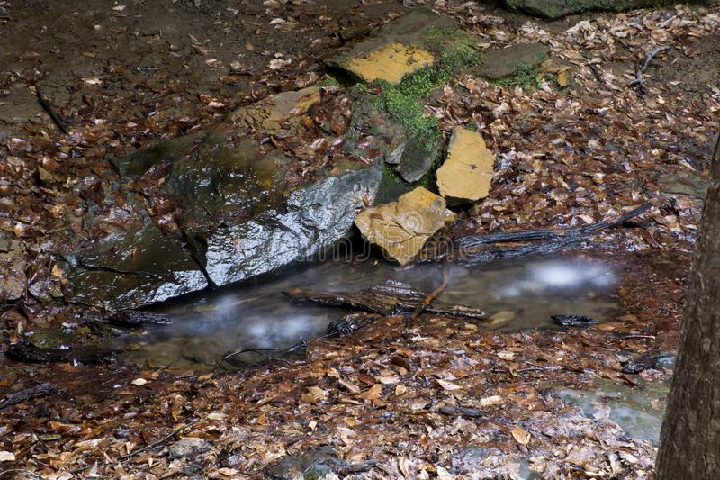 Wter from waterfall landing on rock. The landing area of the waterfalls under the rock bridge in central Ohio near the Hocking Hills area at Rock Bridge Nature royalty free stock image