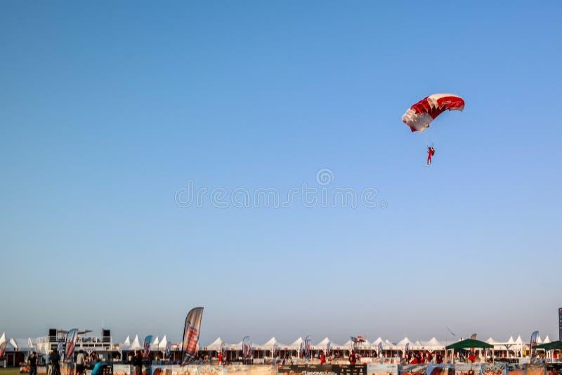 Landing of a fun parachuting activity against a clear blue sky at Dubai Marina.  royalty free stock photography