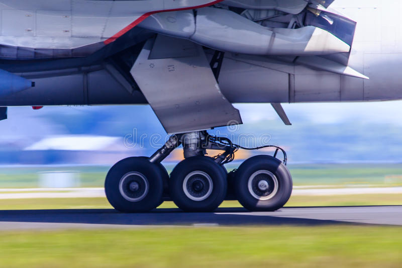 Landing gear in motion. Detail of landing gear of airliner in motion during take-off run royalty free stock images