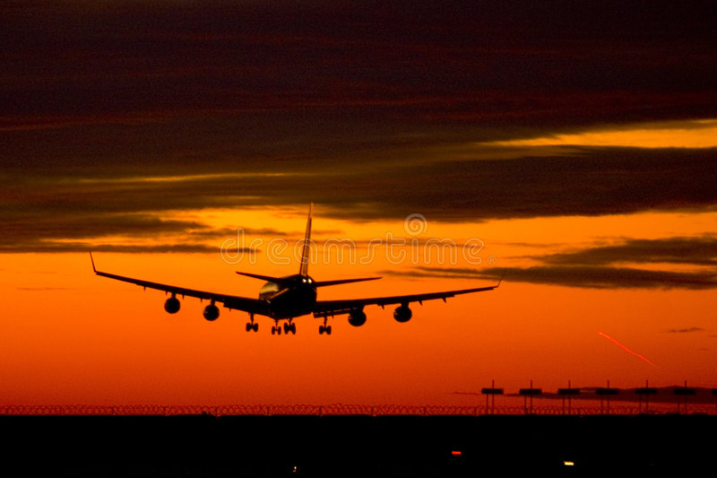 Landing plane on a sunset royalty free stock photos