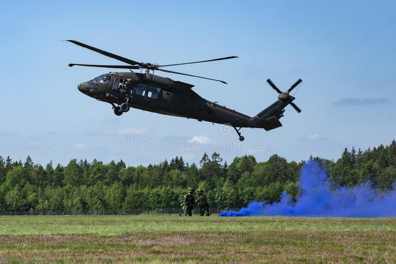 Landing of swedish military helicopter Blackhawk UH-60. Military armed men with smoke bomb near forest under blue sky.  royalty free stock images