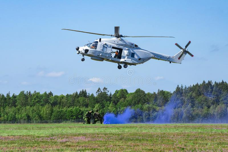 Landing of swedish military helicopter NH90 HKP 14 on airshow at Ronneby flygdag F-17 Military armed men with smoke bomb.  stock photography