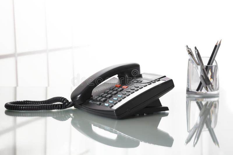 Landliine-Schwarztelefon auf einem Schreibtisch lizenzfreie stockfotos