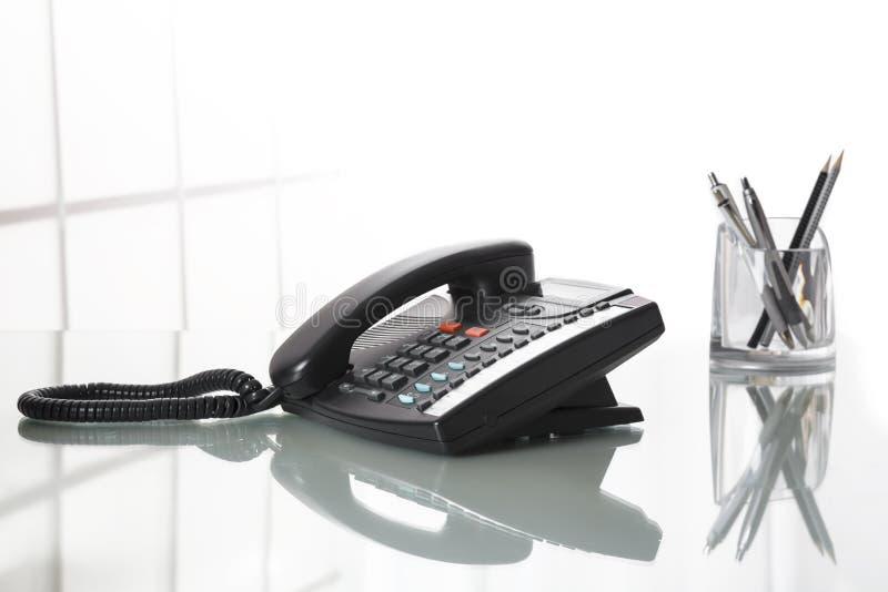 Landliine svarttelefon på ett kontorsskrivbord royaltyfria foton