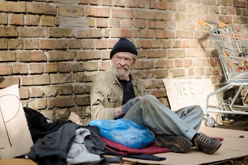 Landloperszitting in de straat, zijn die dingen rond hem worden verspreid royalty-vrije stock fotografie