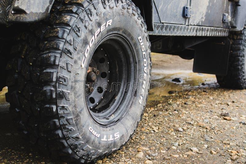 LANDMANNALAUGAR, ISLÂNDIA - EM AGOSTO DE 2018: close-up de pneus todo-terreno do carro na estrada da lama fotografia de stock royalty free
