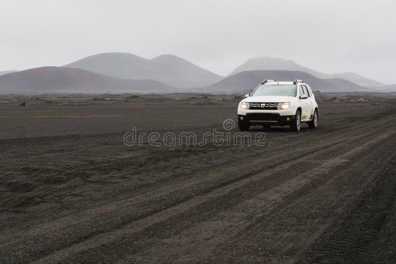 LANDMANNALAUGAR, ISLÂNDIA - EM AGOSTO DE 2018: Condução de carro no campo de lava preto na estrada à área de Landmannalaugar, Isl fotos de stock