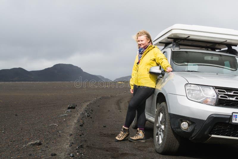 LANDMANNALAUGAR, ISLÂNDIA - EM AGOSTO DE 2018: posição da mulher ao lado de um carro offroad na área de Landmannalaugar, Islândia imagens de stock royalty free