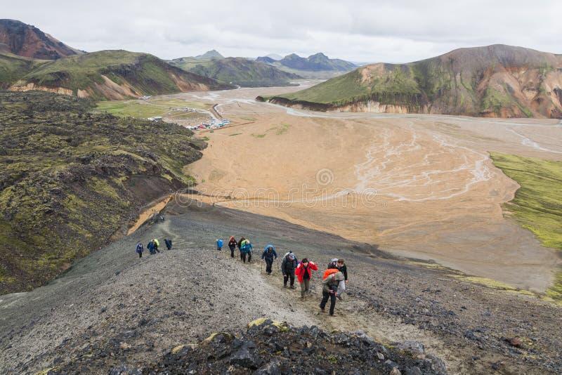 LANDMANNALAUGAR, ISLÂNDIA - EM AGOSTO DE 2018: Turistas que trekking nas montanhas coloridas do parque nacional de Landmannalauga imagem de stock