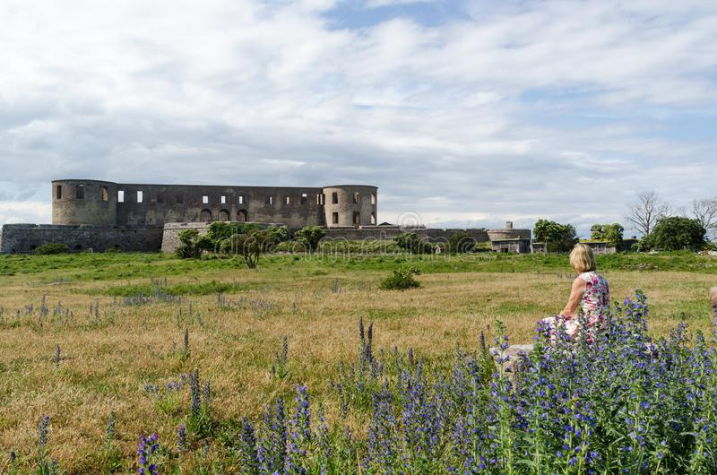 The landmark Borgholm castle ruin in Sweden. With a watching woman and summer flowers royalty free stock image
