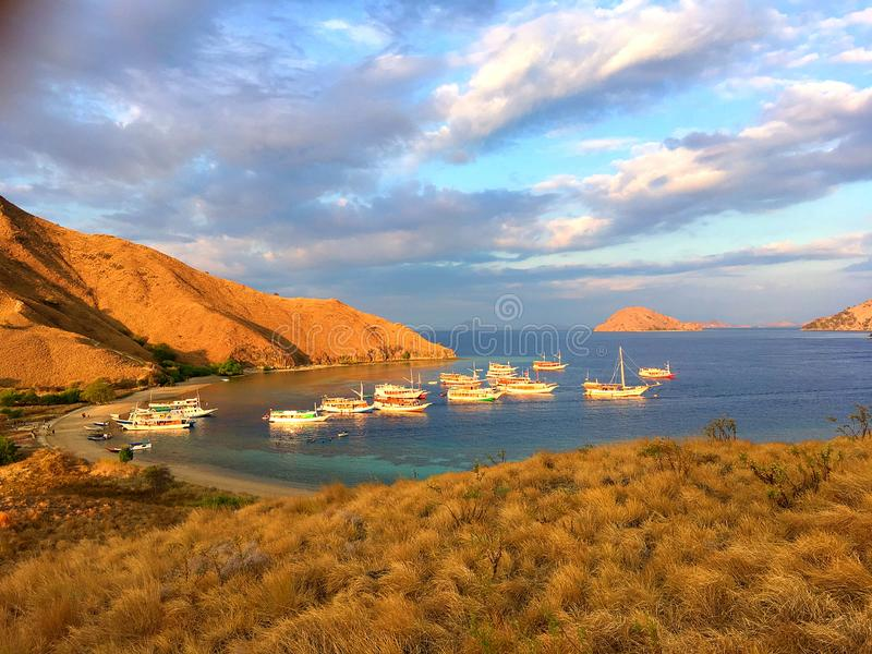 Landmark view of `GILI LAWA DARAT` with green savanna grass and blue sea in an evening, Komodo Island. Landmark view of traveller boat at`Gili Lawa` with green royalty free stock photo