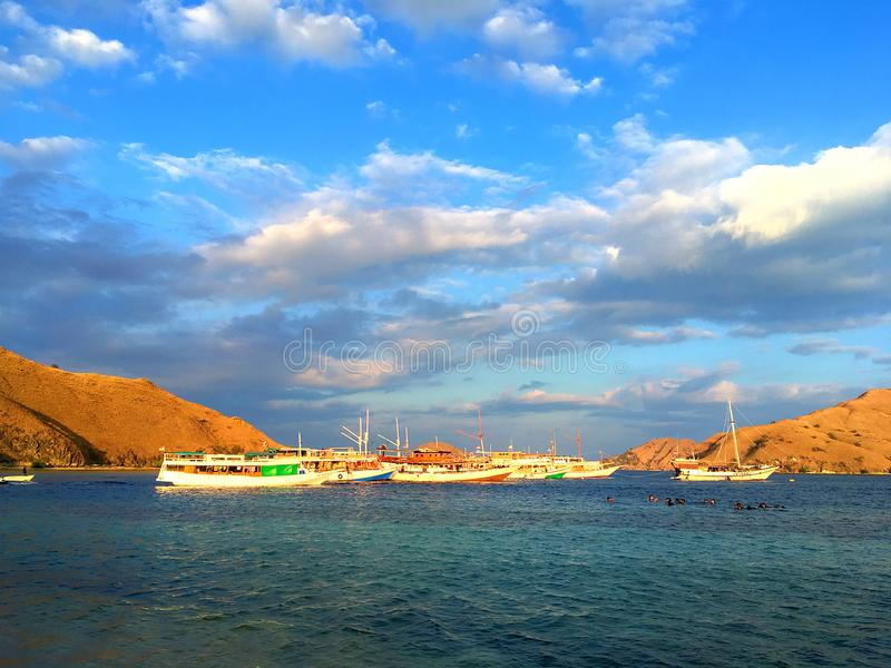 Landmark view of `GILI LAWA DARAT` with green savanna grass and blue sea in an evening, Komodo Island. Landmark view of traveller boat at`Gili Lawa` with green stock photos