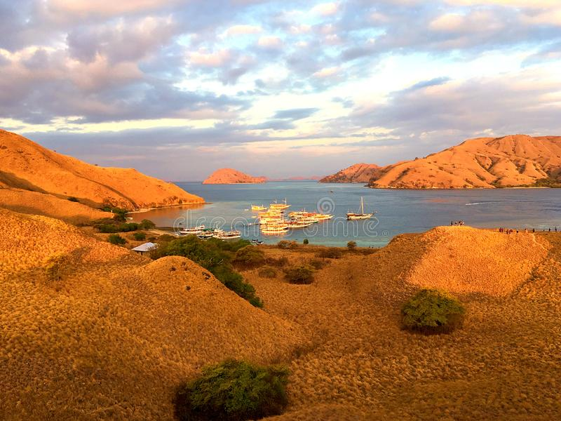 Landmark view of `GILI LAWA DARAT` with green savanna grass and blue sea in an evening, Komodo Island. Landmark view of traveller boat at`Gili Lawa` with green royalty free stock images