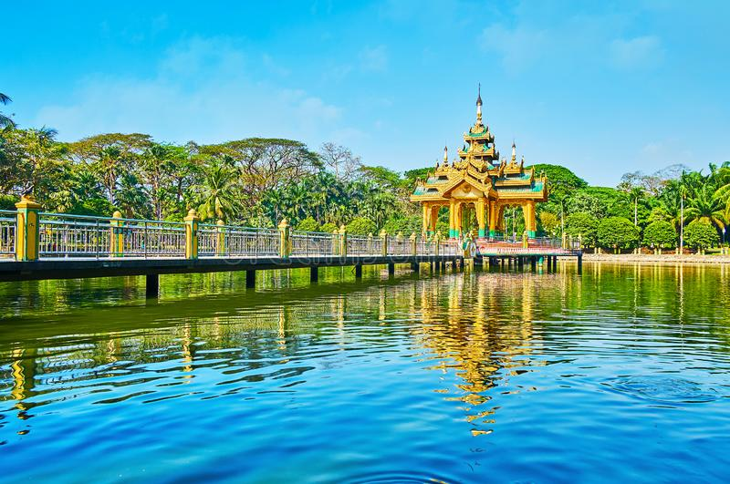 The landmarks of Theingottara park, Yangon, Myanmar. The small Buddhist shrine on the lake of Theingottara park, with a long bridge from both sides and lush stock photography