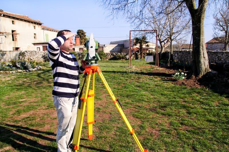 Landmetersarbeider die meting in de tuin maken, totale post stock afbeeldingen