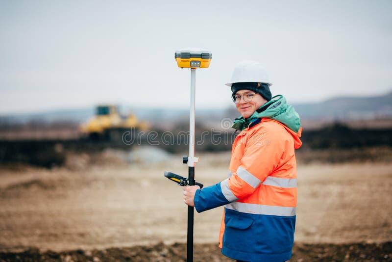 Landmetersingenieur die aan wegbouwwerf werken, die met theodoliet en gps systeem werken stock afbeelding