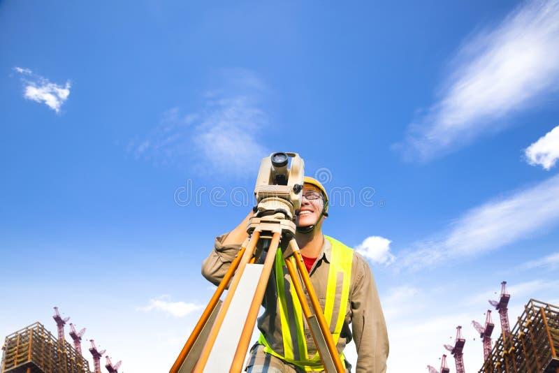 Landmetersingenieur die maatregel op het gebied maken royalty-vrije stock afbeelding